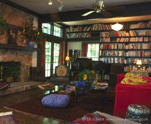 Another view of the great room with it's bookshelves, stone fireplace and grand piano.