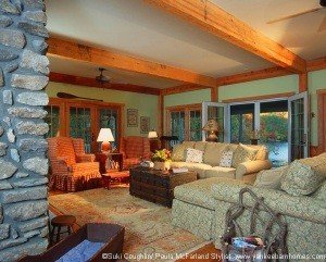 A series of French doors on three sides of the great room open to the wrap around porch and views of the lake.